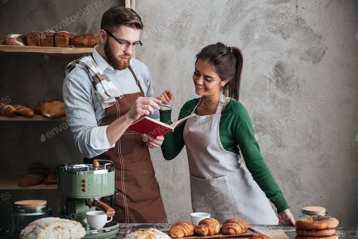 Sonriente pareja amorosos panaderos mirando al cuaderno.