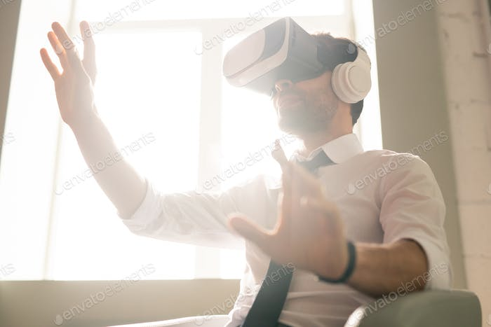 Businessman testing new app in VR goggles
