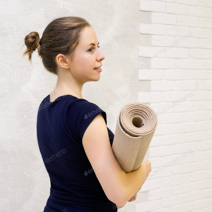 Portrait of woman with yoga mat.
