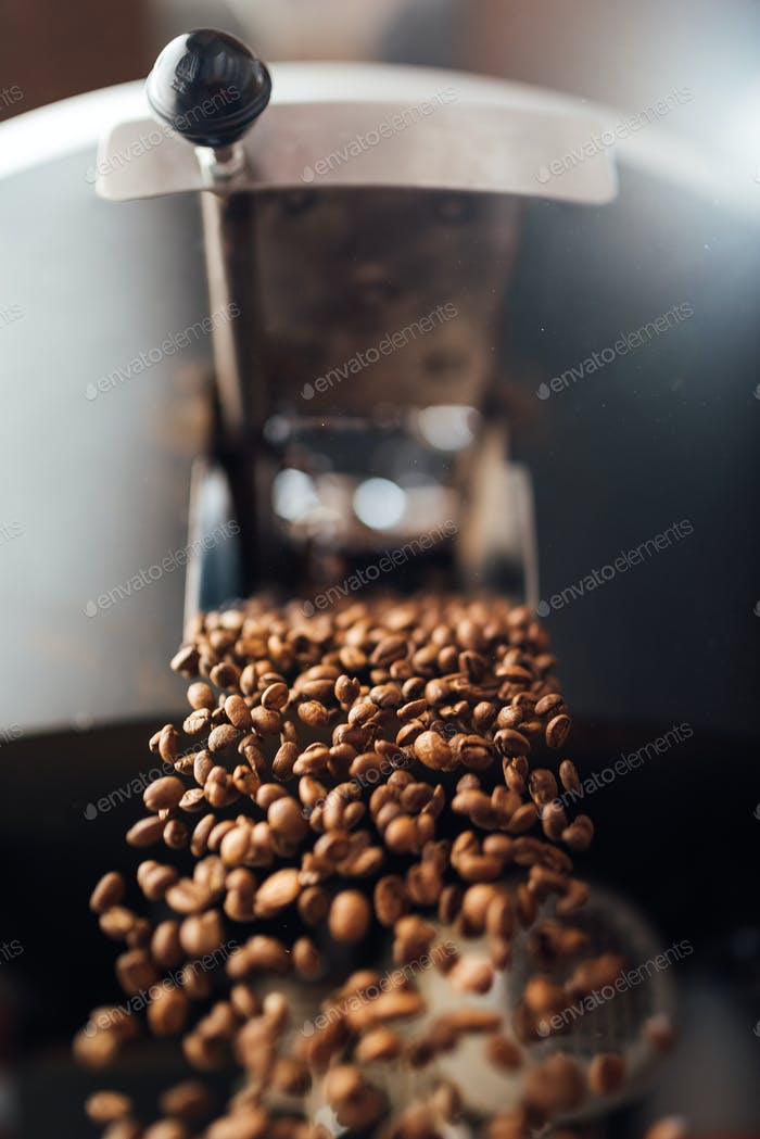 The flow of coffee beans from open flap of the cooling mixer of roasting machine