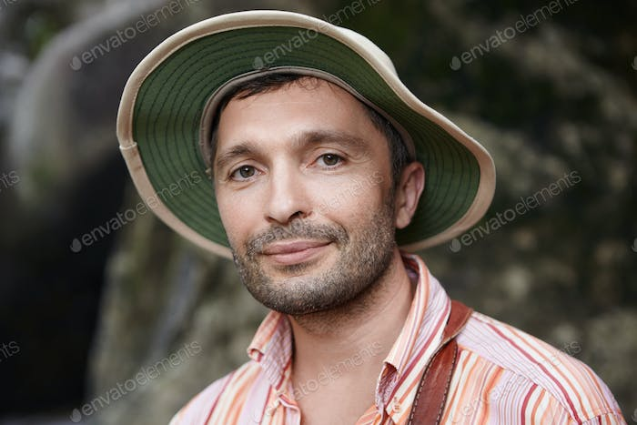 Close up portrait of handsome scientist with small beard wearing panama hat and striped shirt lookin