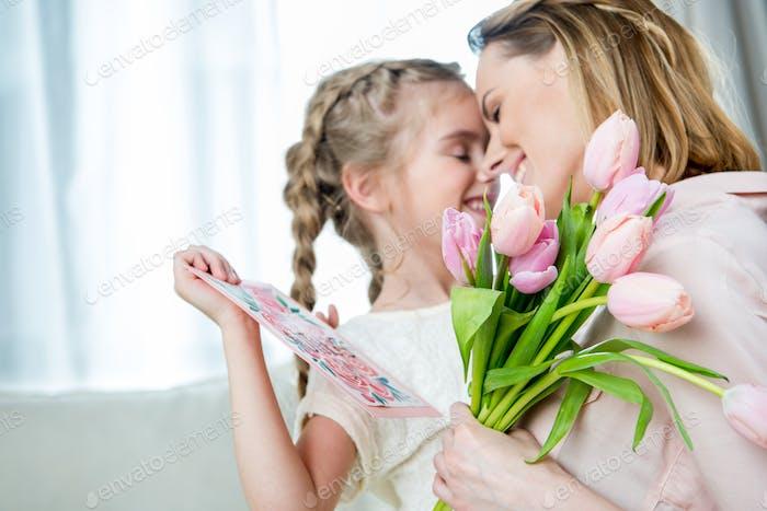 glückliche Mutter umarmt Tochter mit Postkarte am Muttertag