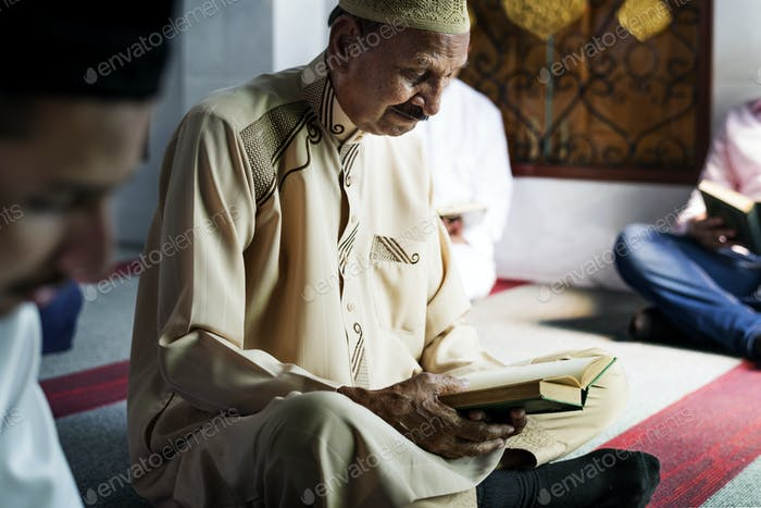 Muslim men reading Quran during Ramadan