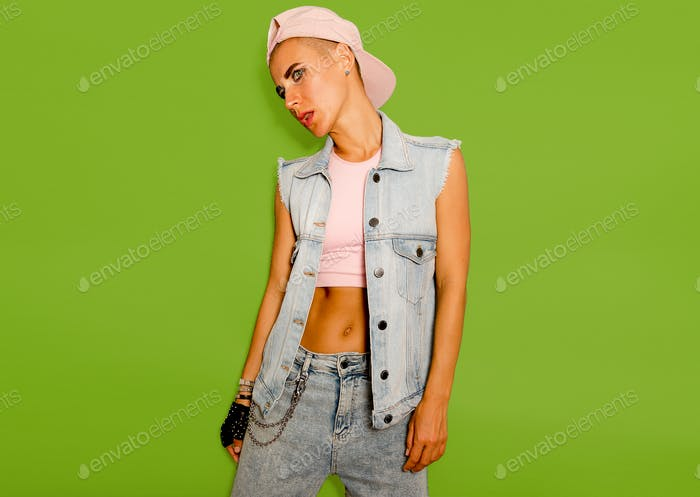 Tomboy model in denim style outfit on a green background