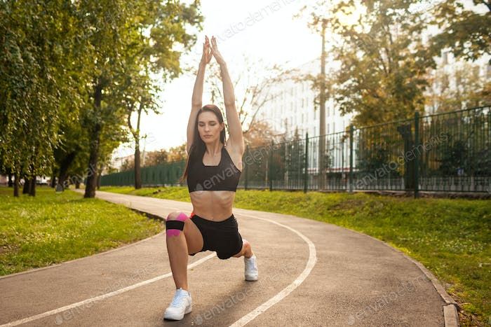 Flexible woman with kinesiotaping training in park