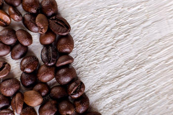 Kaffeebohnen oder Korn auf weißem Holzhintergrund. Flache Lag.