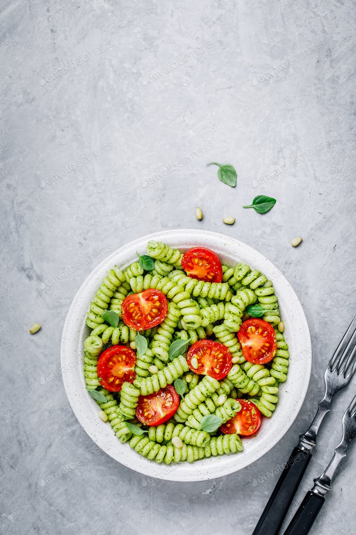 Fusilli pasta with basil pesto sauce , tomatoes and pine nuts.
