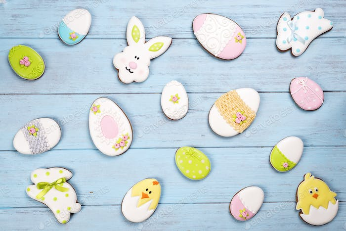 Colorful Easter cookies all over blue wooden background.