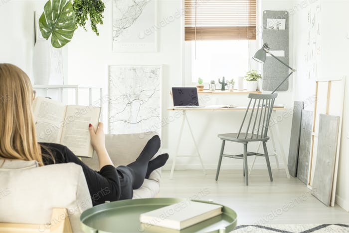Woman reading a book on the sofa in bright home office room inte
