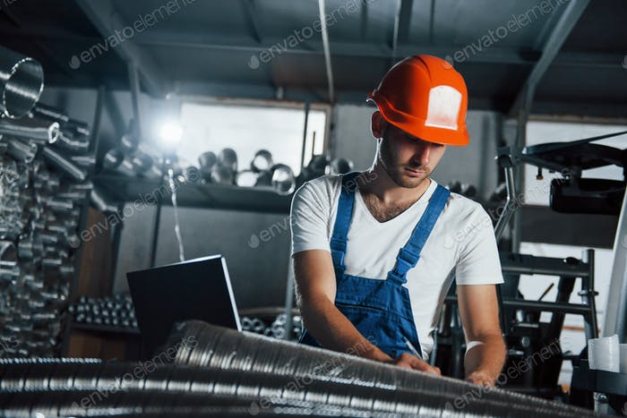 Beleuchtungsgeräte dahinter. Mann in Uniform arbeitet an der Produktion. Industrielle moderne Technik
