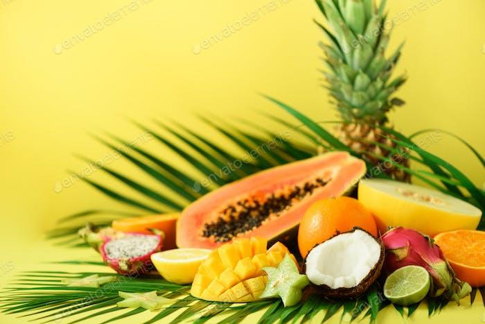Sortiment von exotischen Früchten auf gelbem Hintergrund. Detox, veganes Essen, Sommerkonzept Papaya, Mango