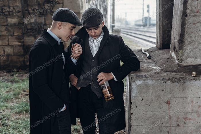 Posing on background of railway with bottle of alcohol