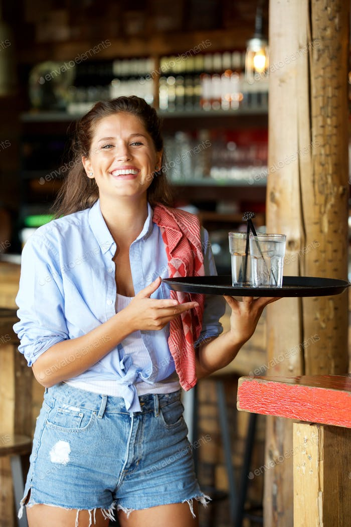 young laughing female server with tray of drinks