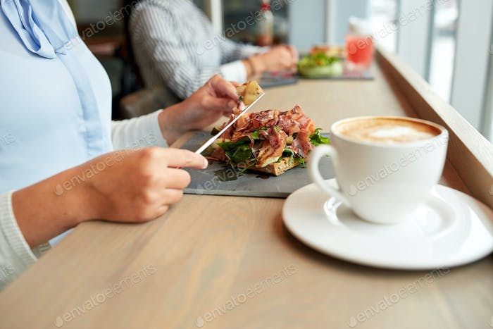 woman eating prosciutto ham salad at restaurant