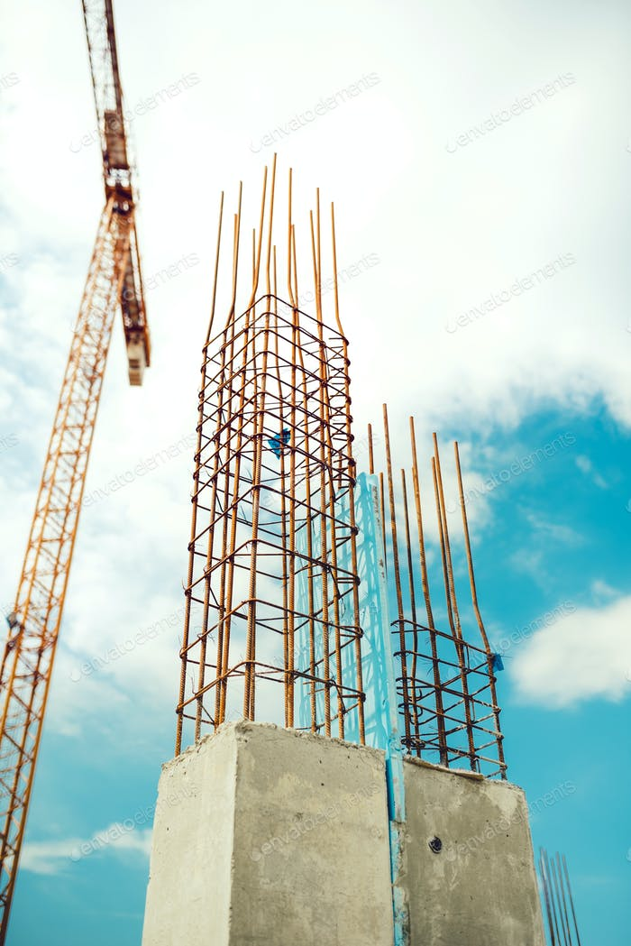 Worker with crane installing prefabricated concrete walls