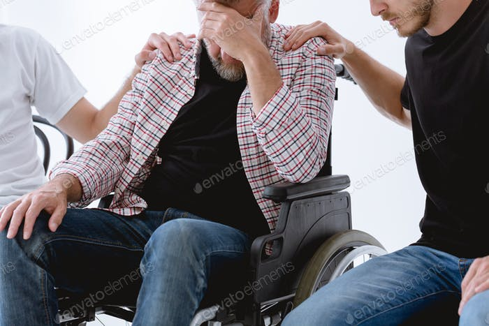 Friends supporting injured man on wheelchair during psychotherapy for people with ptsd
