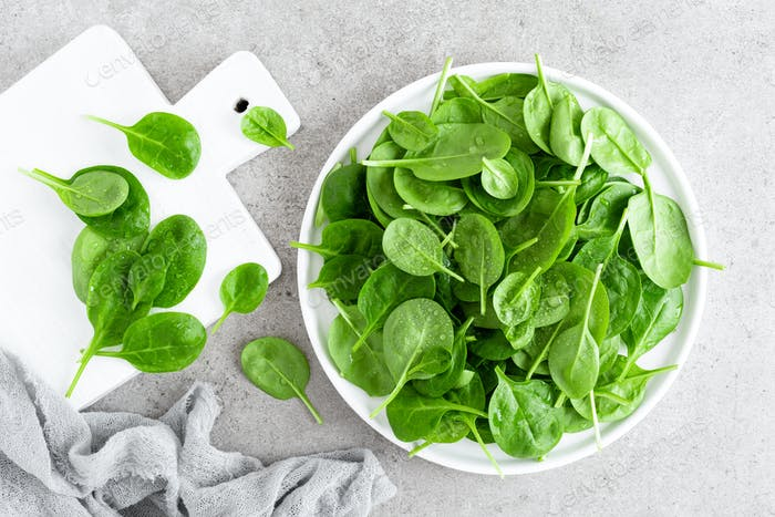Fresh spinach leaves on white plate. Healthy vegan food. Top view