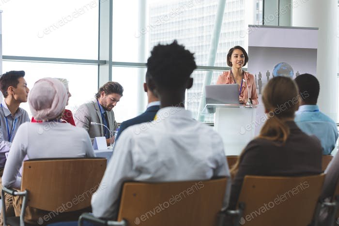 Female speaker with laptop speaking in business seminar in office building