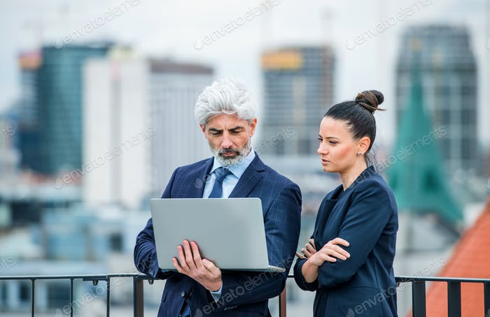 A businessman and businesswoman with laptop standing on a terrace, working