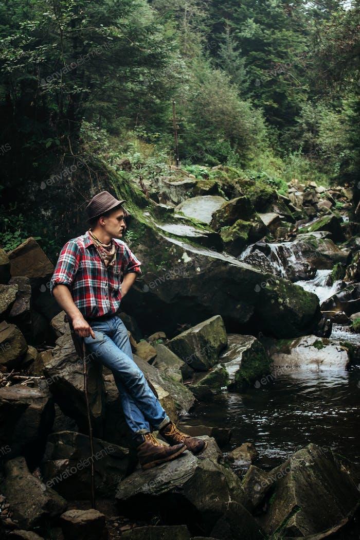 стильный хипстерский лесоруб с топором в солнечном лесу у реки в горах