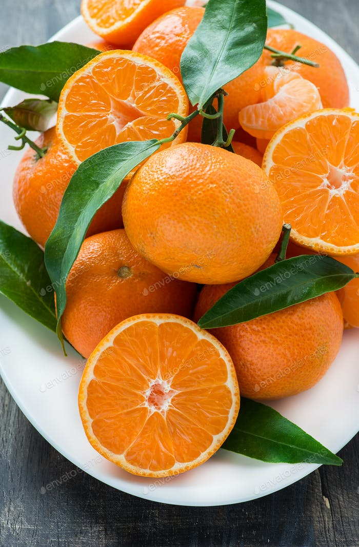 Tangerines with leaves on plate