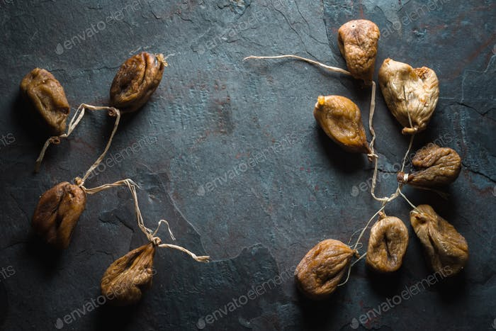 Dried beige figs with a rope on a gray stone on the right and left
