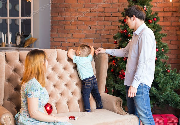 christmas, x-mas, family, people, happiness concept - happy parents playing with cute baby boy