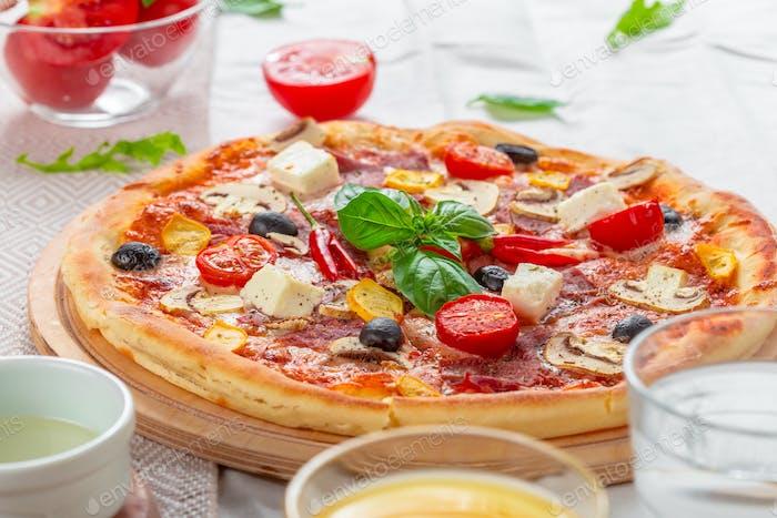Pizza mit Mozzarella, Schinken, Cherrytomaten, schwarze Oliven