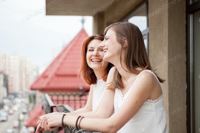 Two female friends talking and laughing at the balcony