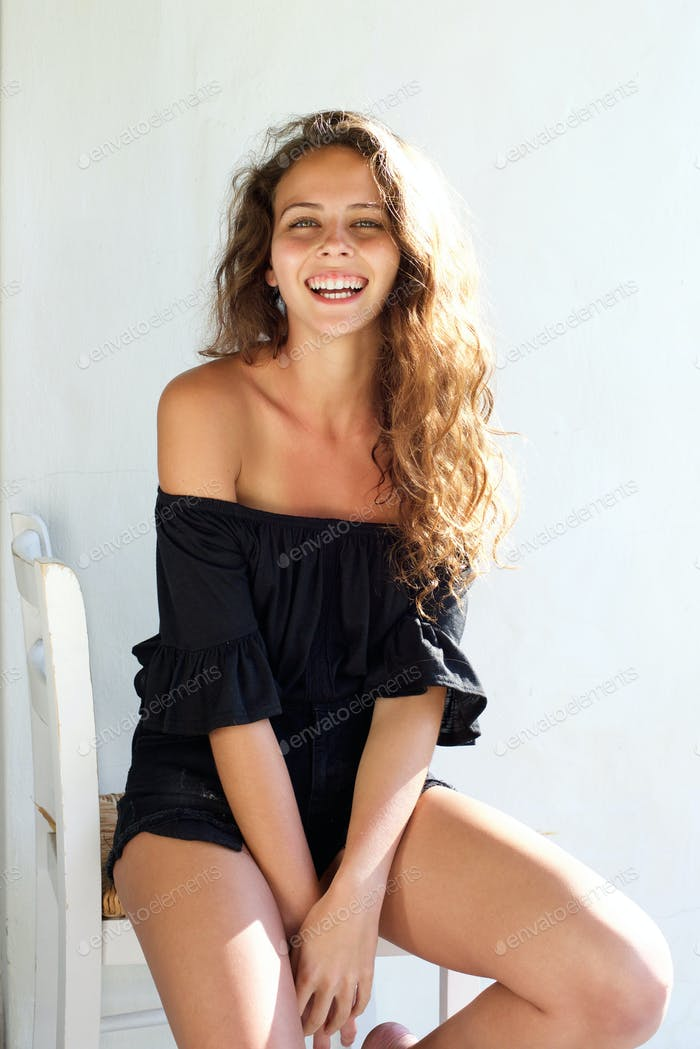 Smiling young beautiful woman sitting on chair