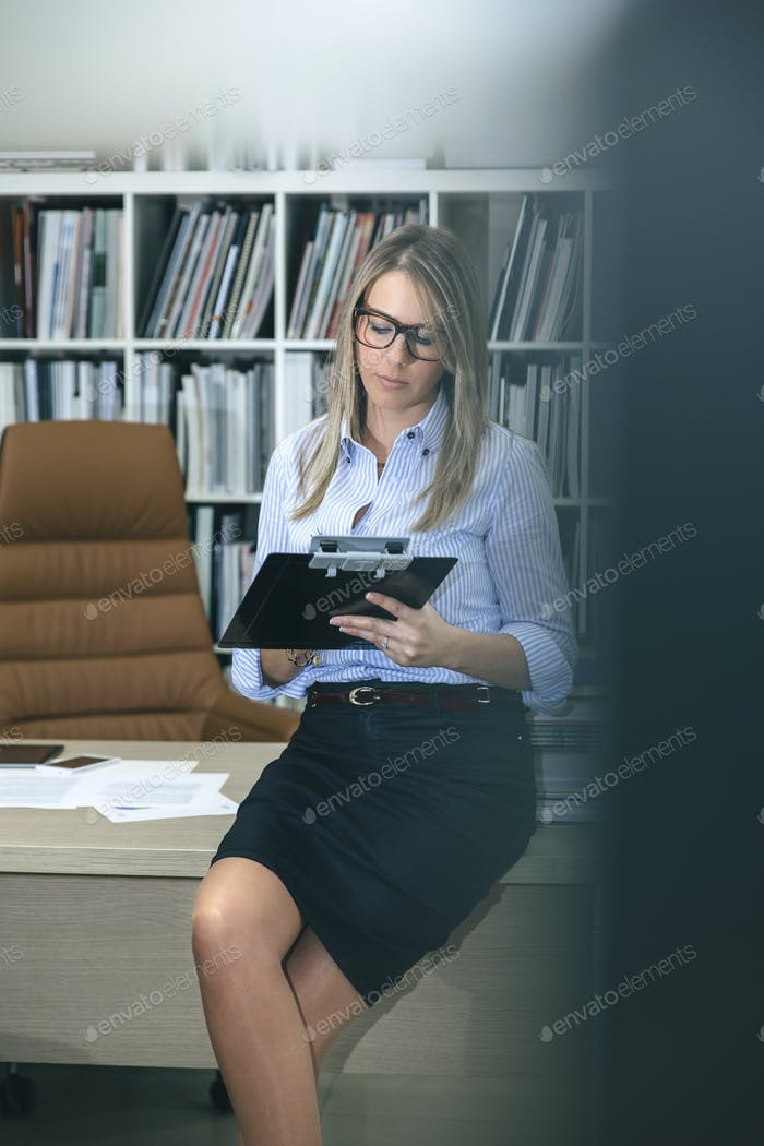 Woman writing notes sitting over desktop table