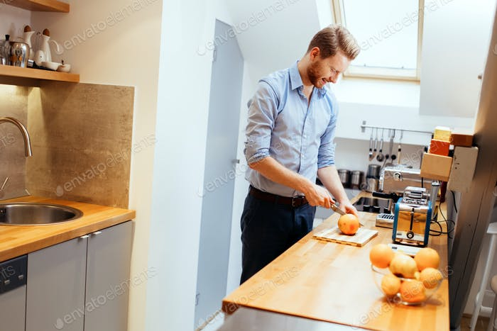 Man slicing oranges in kitchen
