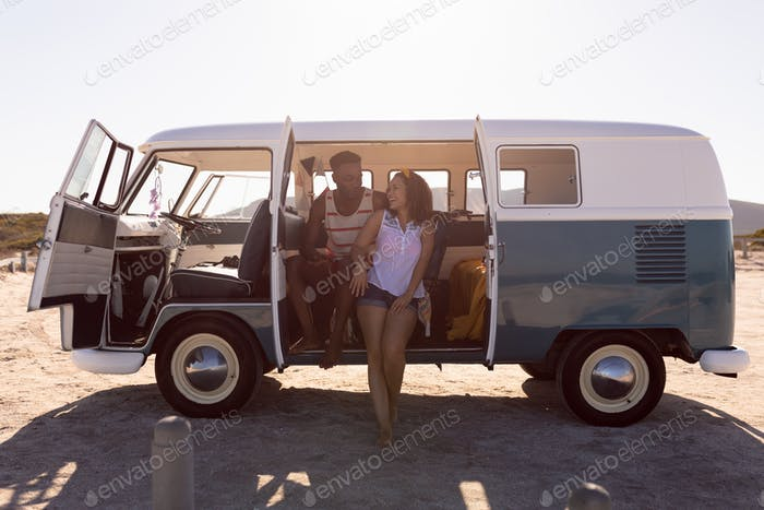 Front view of happy young diverse couple having fun in camper van at beach