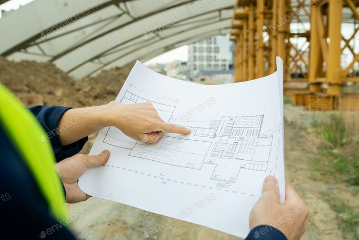 Hand of female engineer pointing at sketch of unfinished construction