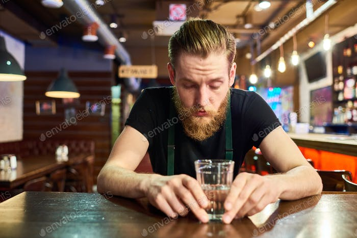Young Bearded Man Getting Drunk in Bar