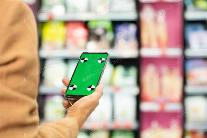 Hand of young female shopaholic holding smartphone with green e-coupon