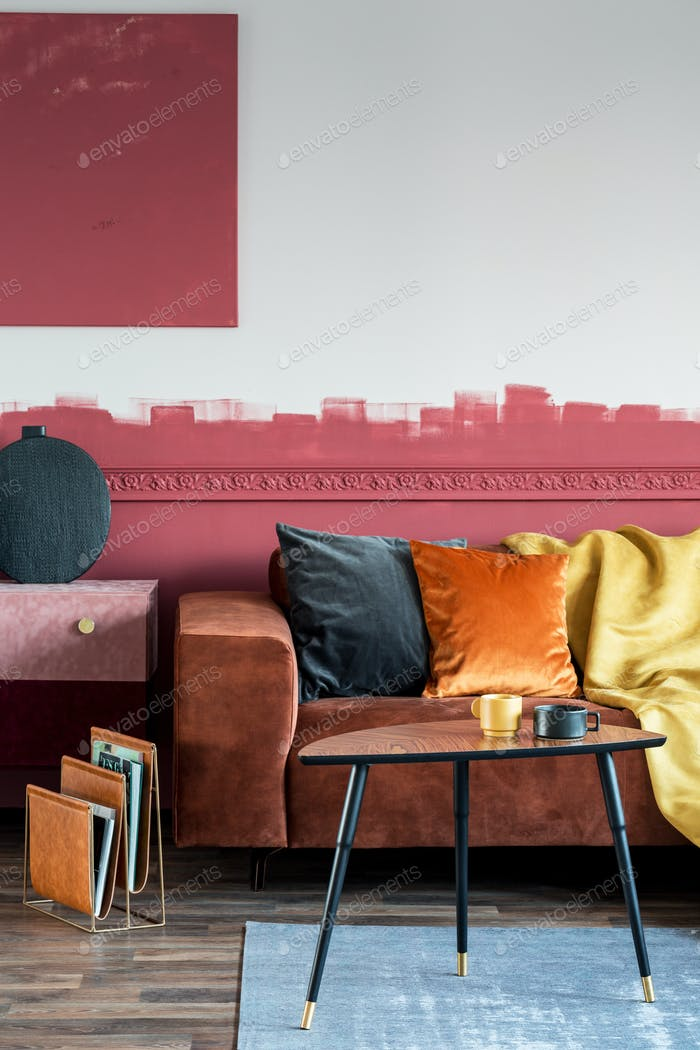 Orange pillow on brown sofa in fashionable living room interior with suede commode