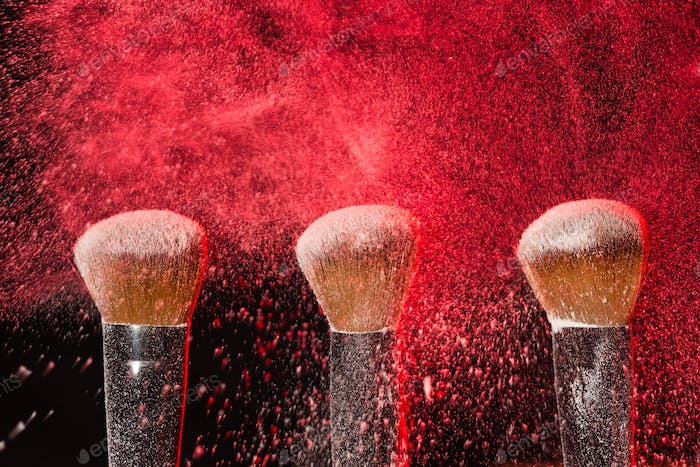 Make up, beauty, mineral cosmetic concept - powder brush on black background with red powder