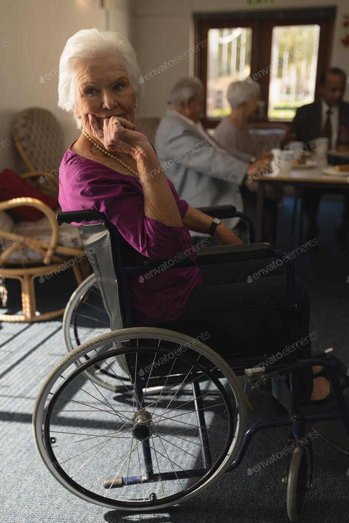 Side view of disable senior woman sitting on whee chair and looking at camera in home