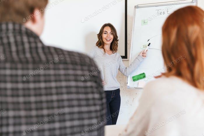 Woman standing near desk holding marker