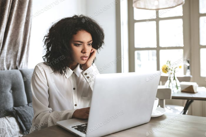 Portrait of concentrated lady that thoughtfully looking in laptop