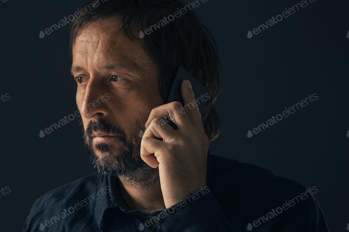Bitter heartbroken melancholic guy talking on mobile phone