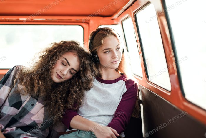 Young female friends on a roadtrip through countryside, sitting in minivan.