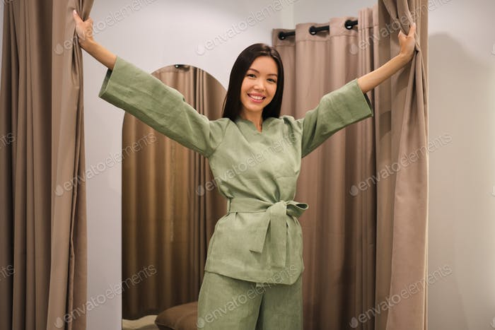 Attractive smiling Asian girl in stylish suit joyfully posing in dressing room of clothes store