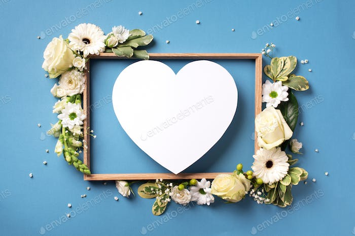 Frame of white flowers, paper heart over blue background. Valentines day, Woman day concept. Spring