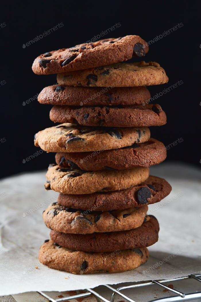 A pile of chocolate cookies with chocolate chips on baking paper