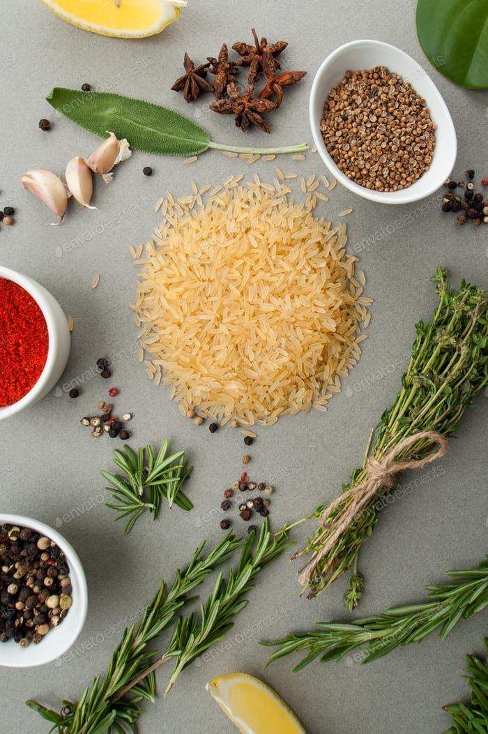 Rice, spicy herbs and spices on a light gray stone table.