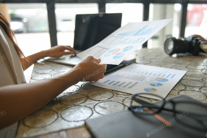 Hand of a business woman is using a laptop to find information.