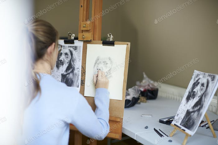 Rear View Of Female Teenage Artist Sitting At Easel Drawing Picture Of Dog