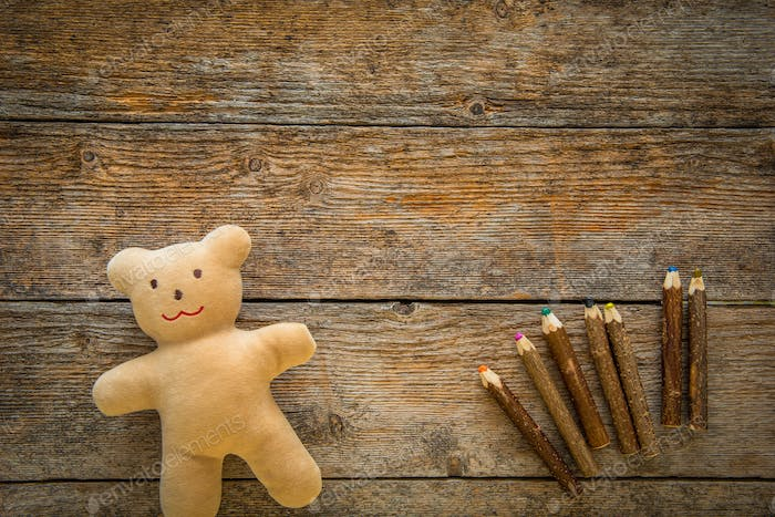 Adorable teddy bear and colored pencils on wooden table. Space for text